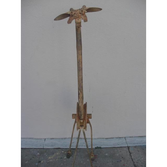 This wonderfully imaginative abstract giraffe sculpture created from salvaged metal objects like a pulley wheel, bicycle...