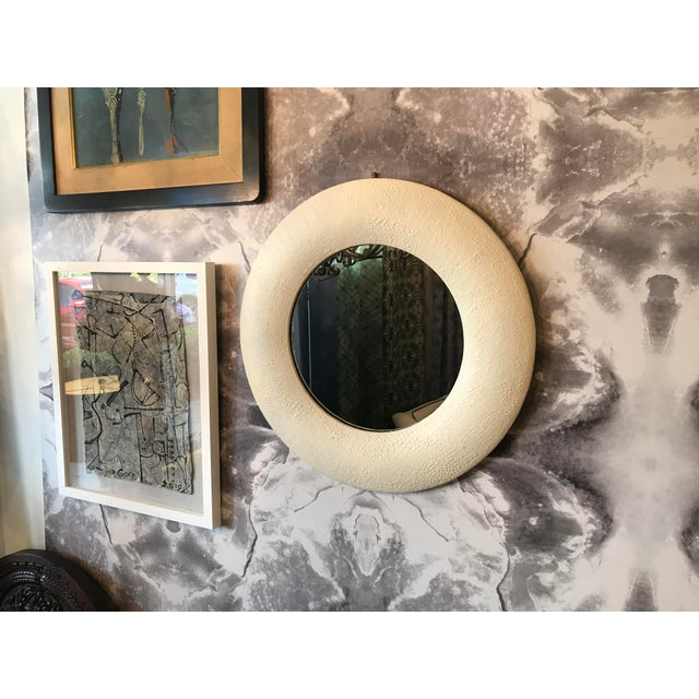 Round offwhite embossed leather mirror. It has a crocodile effect on the leather.