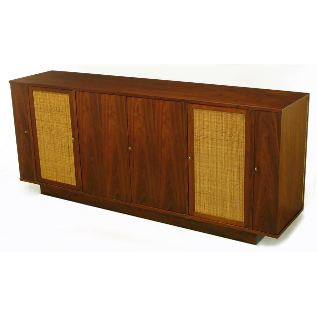 Edward Wormley for Dunbar walnut and cane sideboard on recessed plinth base. Gullwing style side doors open to reveal...