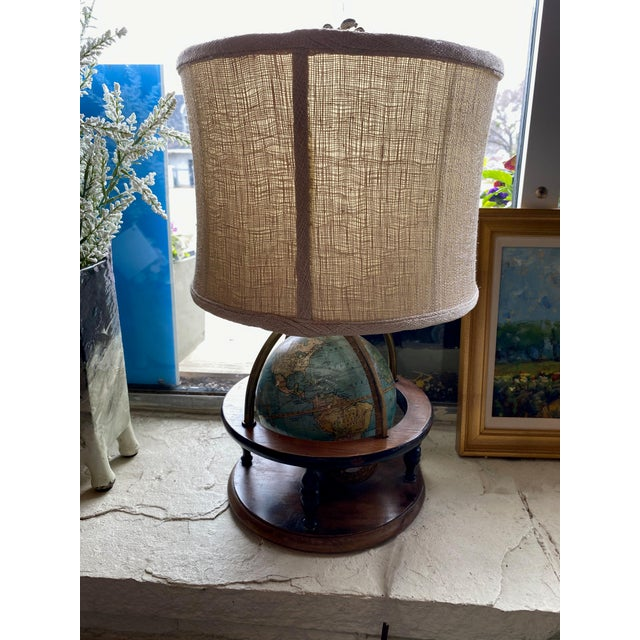 An antique globe lamp with wood surround. Shade and eagle shaped finial appear to be original.