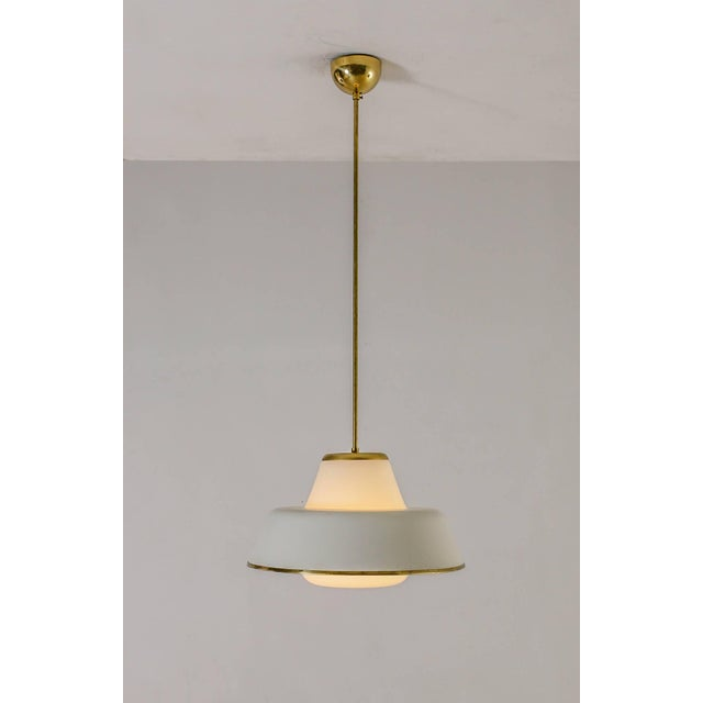 A simple and elegant model 61-347 pendant lamp. The lamp is made of a white glass base with a metal shade and old plastic...