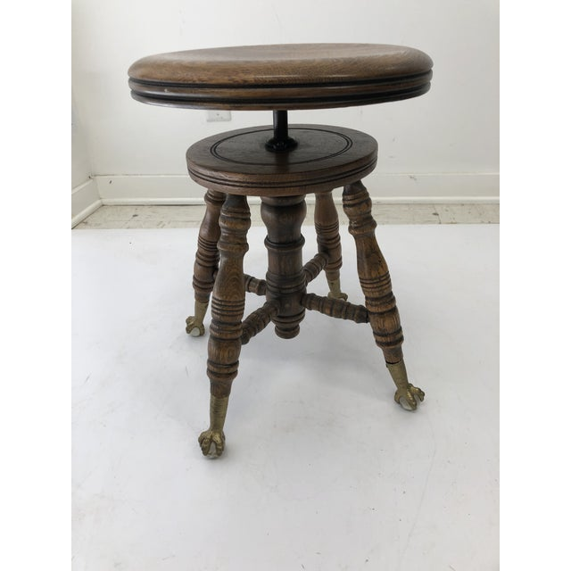 Vintage Wood Organ Stool. Beautiful wood tones. Molded seat. Swivels to adjust up and down. Iron and glass ball & claw...