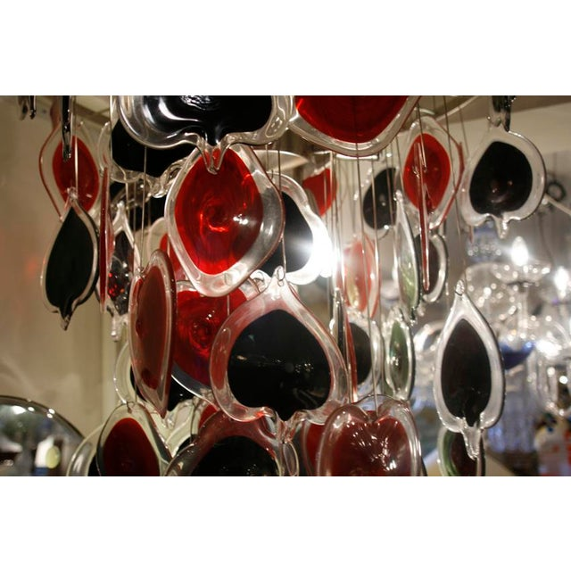 "A unique ""Poker"" ceiling light brush steel frame with glass components in red and black in the shape of the four poker..."