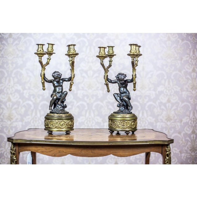 We present you this mantel clock set with putti composed of a mantel clock and two four-arm candelabra. The putti are made...