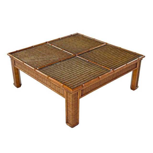 Vintage 1970s monumental boho wicker and rattan coffee table. Four in-set glass panels add a touch of elegance and enhance...