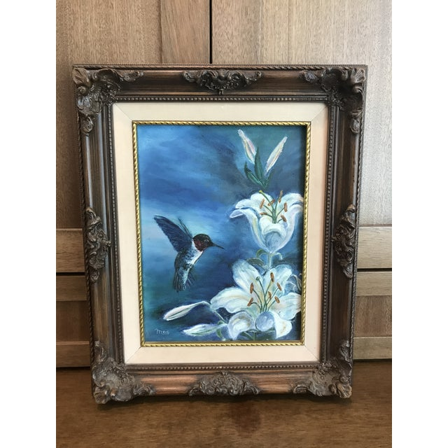 This is a vintage oil on canvas painting. Hummingbird and white flowers with a blue background. Solid wood frame with...