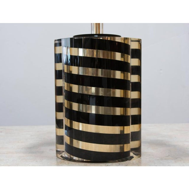 Black and gold diagonally striped round base is encased in ellipse or almond shaped Lucite. The difference in the two...