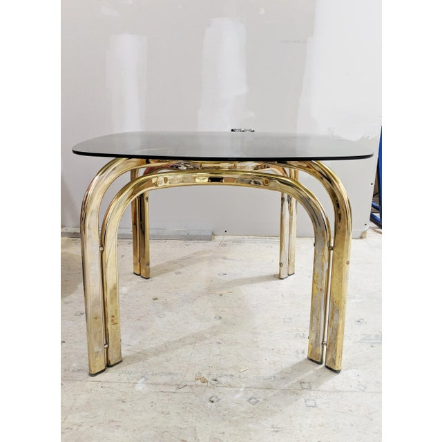 An incredibly unique vintage coffee table featuring ribboned legs, with a plated brass finish and smoked glass top. Wear...