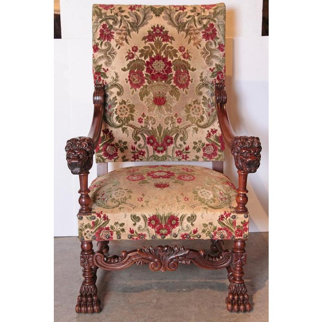 These antique Louis XIV style armchairs have been hand carved out of French walnut wood and upholstered in a floral and...