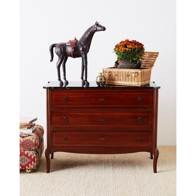 Stately mahogany neoclassical style commode or chest of drawers featuring a polished black marble top. The mahogany case...