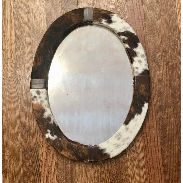 Decorative Oval wall mirror, made of genuine hide and leather accents, mirror is antiqued and there is a chain for hanging...