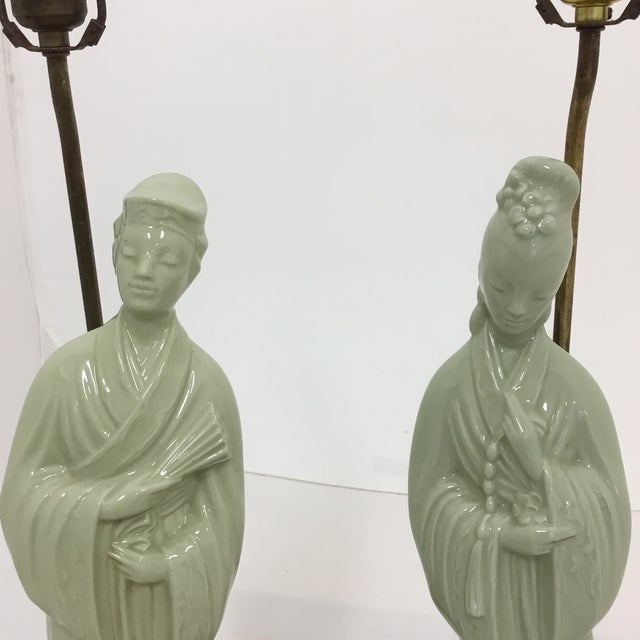 A tall elegant pair of Asian porcelain table lamps with a beautiful celadon finish. The man and women each stand on an...