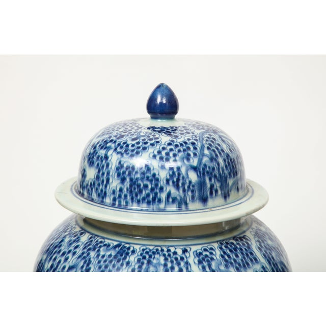 A pair of Chinese export urns with lids featuring a unique design. These would look fabulous on a mantel, flanking a...