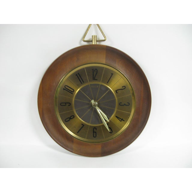 A Mid Century Modern wall clock by Elgin. The clock has a wood/bronze tone dial with brass hands and numbers bordered by...