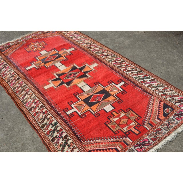 A beautiful, hand knotted vintage Persian Kazak area rug with three center geometric medallions on a solid deep red field....