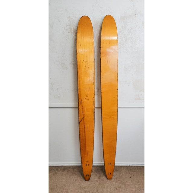 A pair of mid century wooden water skis by Jet Ski. Warm wood with a pop of bright green. A perfect statement piece for a...