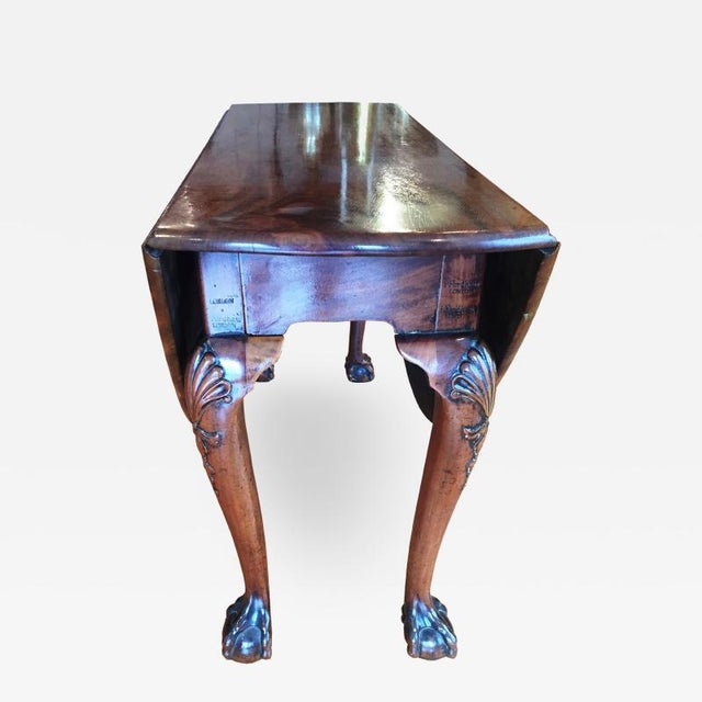 Exceptional oval drop leaf table Cabriole legs with shell carving to the knees, terminating in a bold ball and claw foot....
