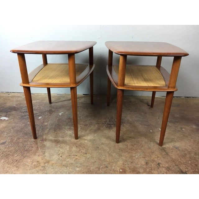 Solid teak end table pair designed by Peter Hvidt and Orla Mølgaard-Nielsen for France & Sons. The lower shelves retain...