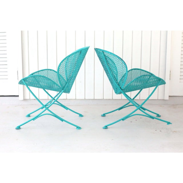 A pair of 1960's low and curvy wrought iron clamshell outdoor chairs. Good vintage condition; minor wear consistent with...