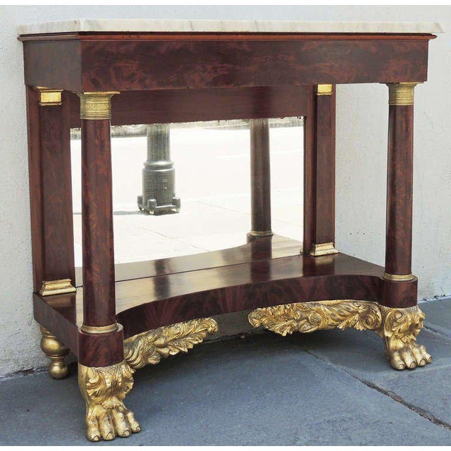 A 19th century New York marble-topped console with a mirrored back, gilt paw feet, and foliage decoration.