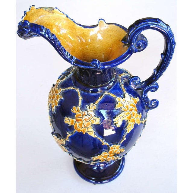 An exuberant pair of Italian cobalt glazed majolica ewers with raised decoration; each large ewer with pinched mouth and...