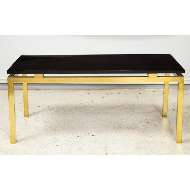 Modern coffee table with lacquered top on brass base.
