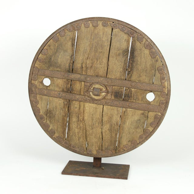 A primitive large oak and iron wheel, circa 1700 on later iron stand, Syrian – a substantial freestanding wheel that can...