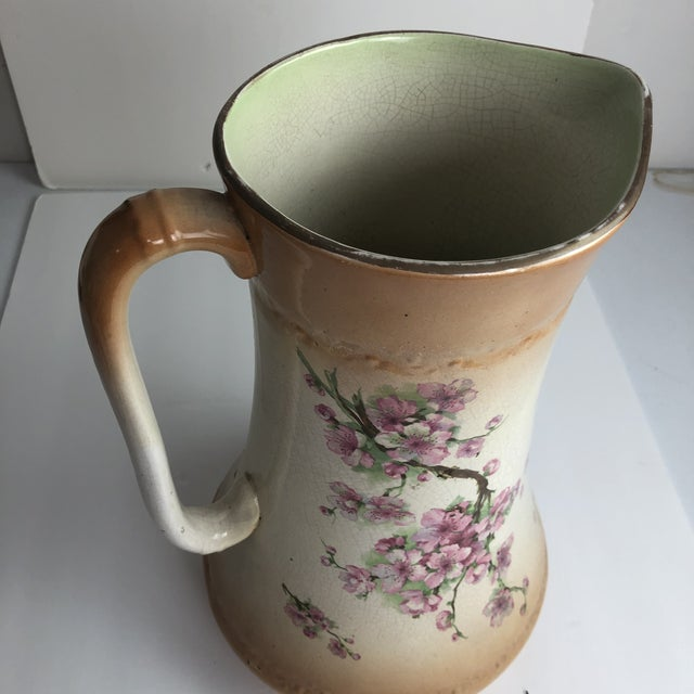 This is a beautiful hand painted large pitcher that MAY have been used at one time with a basin atop a bedroom dresser. It...