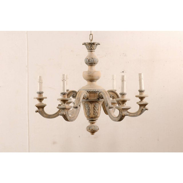 A French vintage carved and painted wood six-light vintage chandelier. This lovely French chandelier from the mid-20th...