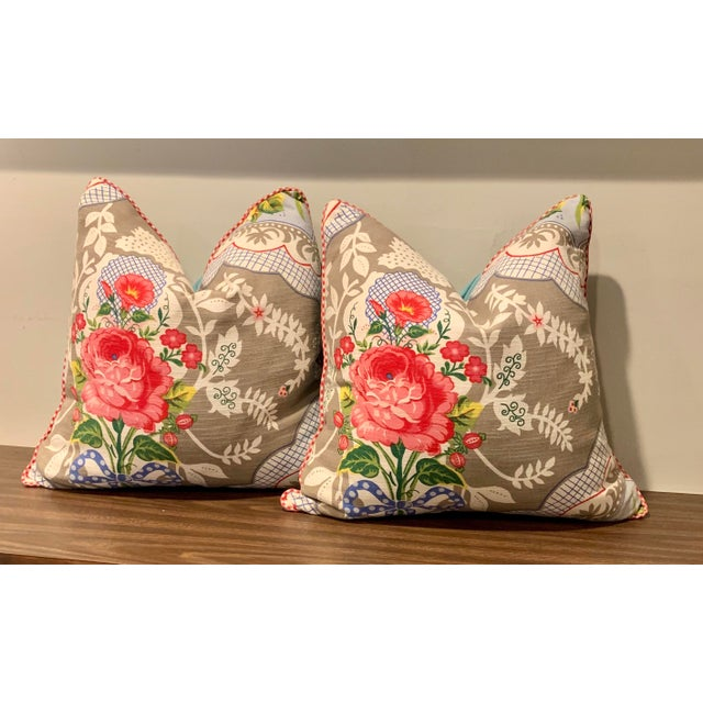 A pair of large European Pip Store pillows in a floral fabric . Light turquoise fabric backs and red check cord trim....