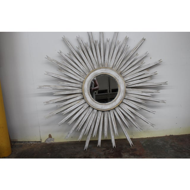Beautiful 20th century vintage sunburst mirror made of gilt wood and finished with a distressed gray wash. This piece...