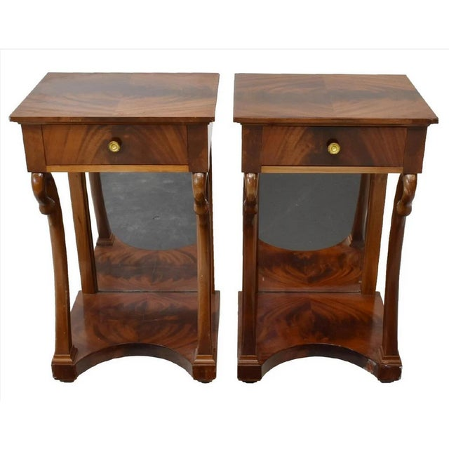 Fine and rare French Empire style mahogany nightstand or side table pair from the early 20th century. The top and lower...