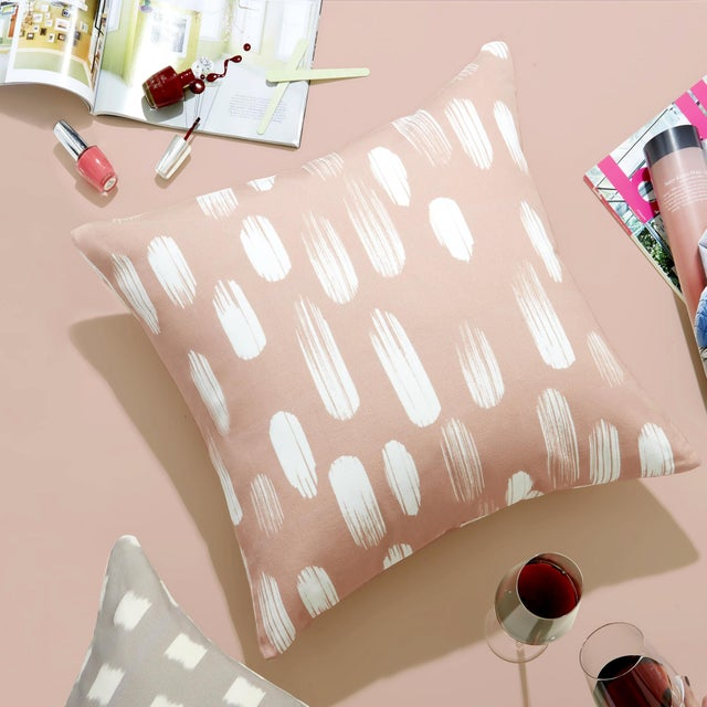 The Carolina print by Pepper Home modernizes the classic polka dots motif with white brushstrokes and adds a pop of color-...