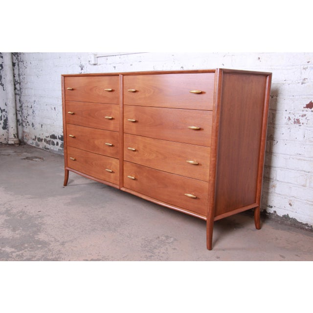 An extremely rare and exceptional mid-century modern sculpted walnut saber leg double dresser designed by T.H. Robsjohn-...