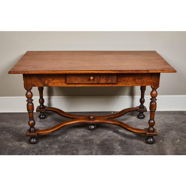 An 18th century Louis XIII walnut library table with a single drawer. Turned legs and stretcher details add a bit of...