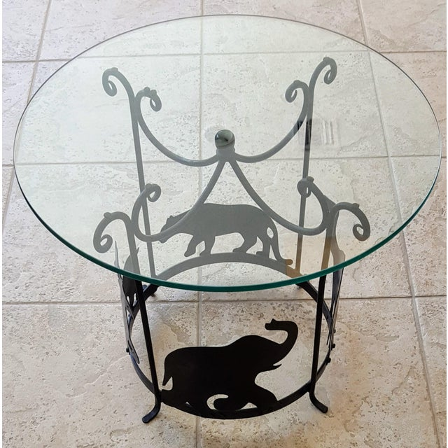 "Hand crafted iron carousel side table with 1/2"" glass top. An elephant, stagg, and lion ""travel"" along the bottom of this..."