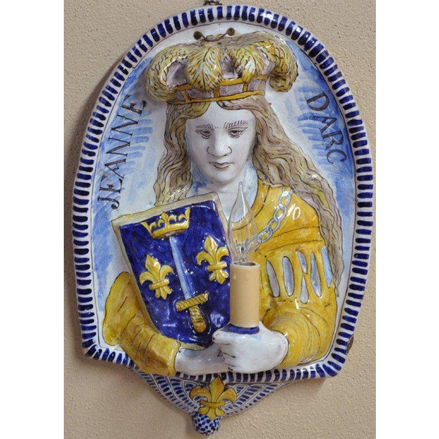 Wonderful pair of medieval colorful antique faience sconces from France, circa 1870, featuring Joan of Arc (1412-1431) and...