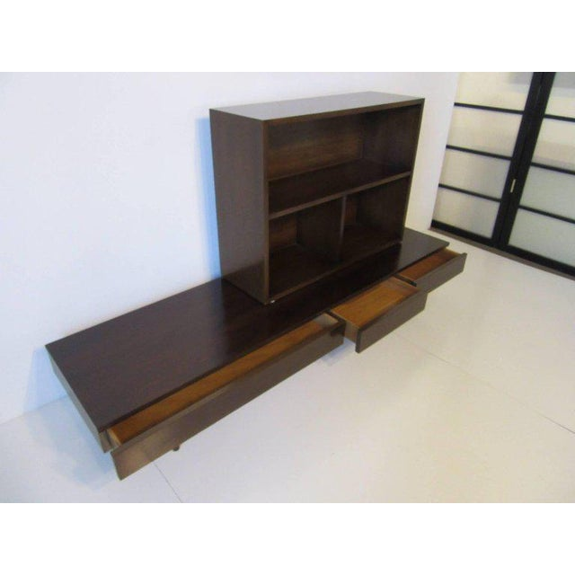 A two-piece ebony finished bookcase set with a lower three drawer platform accented with brass bands and having a upper...