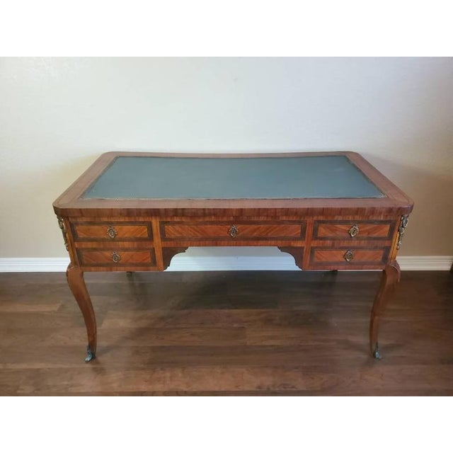 A stunning antique Louis XVI style writing desk with beautifully aged patina. Handcrafted in France in the early 20th...