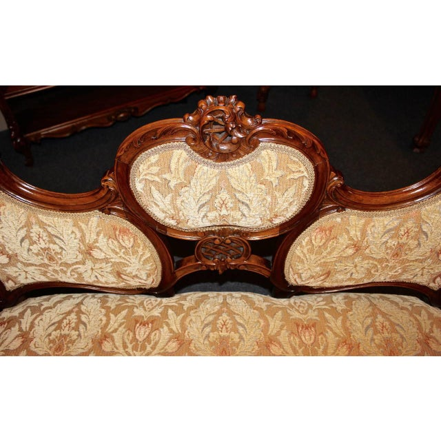 This beautiful French settee is made in the Louis XV style from walnut. The carving on the piece features a crown and...