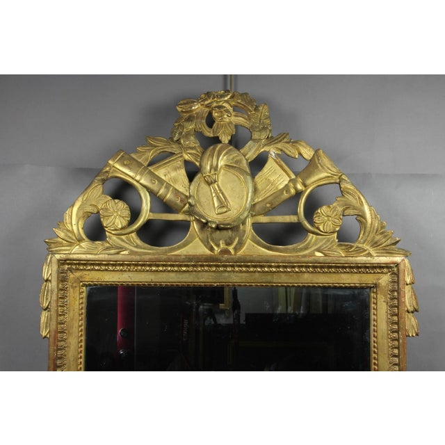 The arched cornice with musical trophy decoration over a beaded and leaf tipped frame.