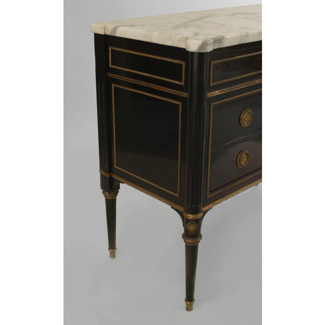 French 1940s (Louis XVI style) ebonized commode with bronze trim and having a single top draw over two larger drawers with...