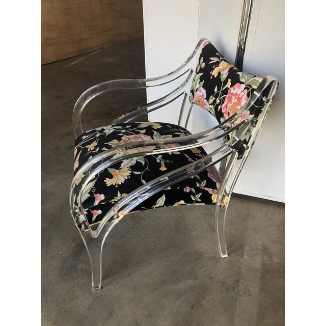 Stylish Lucite bergere chair with curves galore, circa 1980s. Original chintz floral upholstery is in excellent condition....