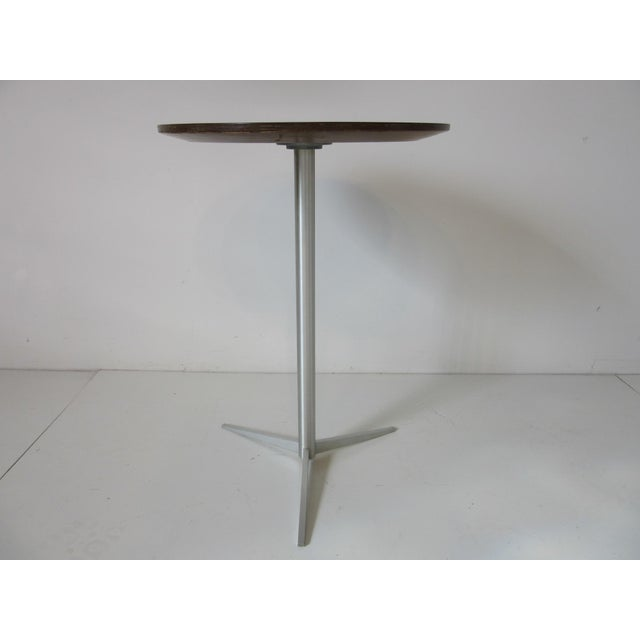 A simple but well constructed drink table with brushed aluminum base and star legs topped with a beveled round laminate...