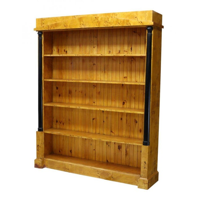 This Danish Biedermeier style birdseye birch bookcase features a pediment faced cornice over five fixed shelves. The back...