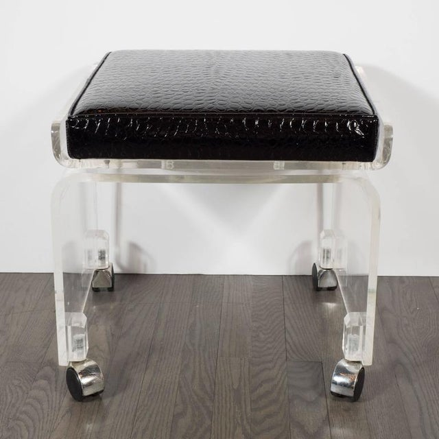 A Mid-Century Lucite swivel chair in newly upholstered faux crocodile fabric. A waterfall design is a single piece of...