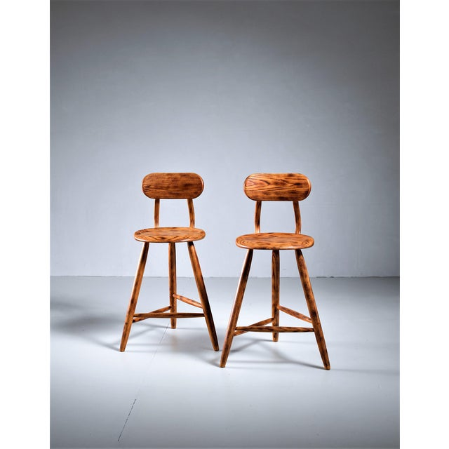 A pair of wooden studio stools with a removable, low backrest. These pieces were made by Pennsylvania craftsman Kai...