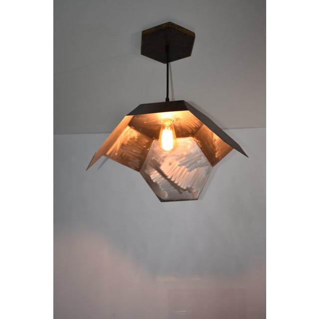 Geometrically inspired ceiling light pendant designed and fabricated by Oblik studio in Brooklyn NY. The exterior is...