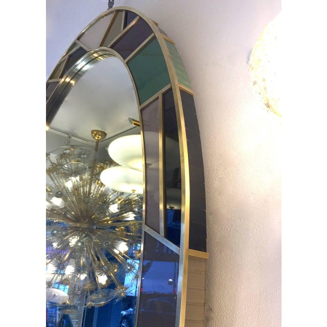 An Italian one-of-a-kind colorful oval mirror of grand size and modern design, entirely handmade. The central oval plate...