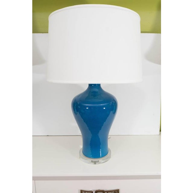 A large Chinese porcelain vase in a stunning blue converted to a lamp on a glass base with shade.